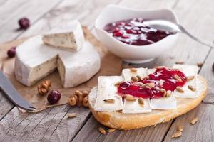 bröd serverat med camembert och tranbär. foto