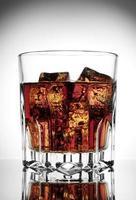 fasetterat glas cola med is foto
