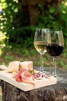 rött och vitt vin i ett glas med korv och skinka foto