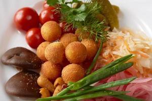 närbild av ostbollar och inlagda grönsaker foto