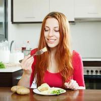 avslappnad positiv tjej som äter potatis foto