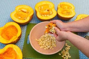 kock som extraherar frön från en pumpa foto
