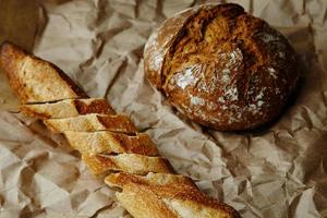 skivad baguette och rågbröd på hantverkspapper foto