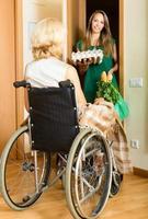 kvinna i rullstolsmöteassistent foto