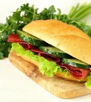 färsk smörgås med rökt kött, gurka och sallad foto
