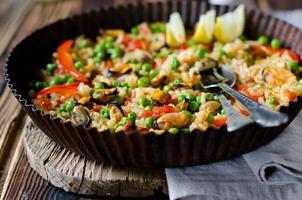 paella med musslor och gröna ärtor foto