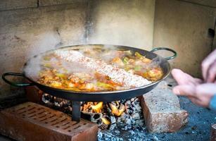 matlagning och framställning av en traditionell spansk paella över öppen spis foto