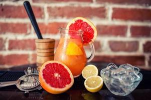 färsk grapefruktlimonad med limefrukter och citroner i kannan foto