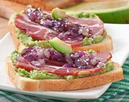 smörgås med skinka, avokadosås och karamelliserad lök foto