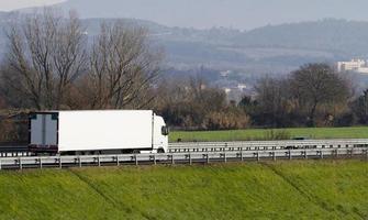 vit lastbil på motorvägen foto