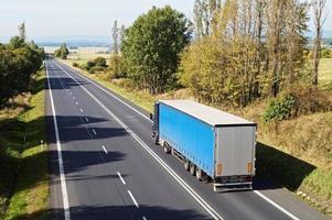 väg mellan träden i ett lantligt landskap. blå lastbil. foto
