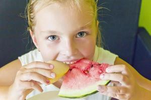 söt flicka äter vattenmelon och melon foto