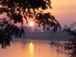 Egypten luxor - solnedgång vid gudarnas flod ... foto