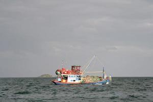 trä lokal fiskerbåt vid havet foto