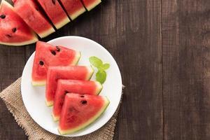 organisk färsk vattenmelon skuren i kilar på träbakgrund foto
