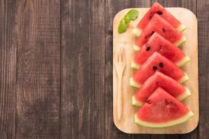 färska vattenmelonstycken placerade på träbakgrund foto