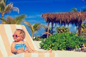 söt liten flicka som dricker juice på tropisk strand foto