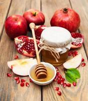 honung med granatäpple och äpplen foto
