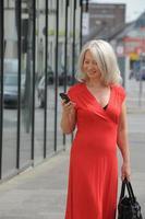 äldre kvinna som använder mobiltelefon utomhus foto