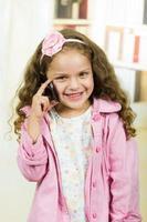 söt liten flicka som använder mobiltelefon foto