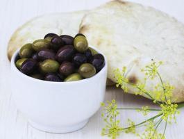 skål med oliver och pitabröd med fänkålblomma foto