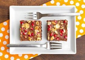 chokladkaka dekorerad med granatäpple och mandel foto