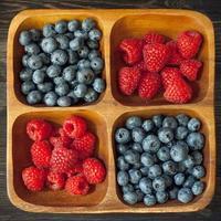 träskål med hallon och blåbär foto
