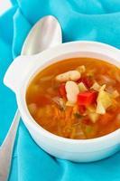 grönsakssoppa i skål och sked foto