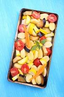 råa grönsaker (potatis, zucchini, tomat, aubergine, morötter) för bakning foto