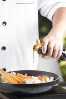 kock som häller shoyusås i pannan foto