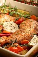 kycklingben med grönsaker och örter redo för rostning foto