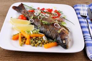 grillad öring och helt olika grönsaker med bestick foto