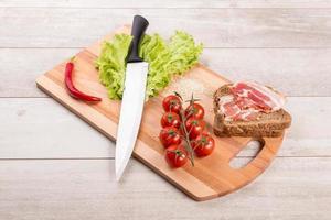 tomat, rostat bröd, kött och sallad på träbord foto