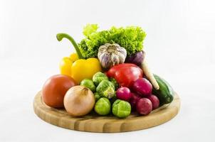 färska grönsaker på träplatta foto