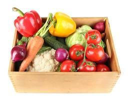 färska grönsaker i trälåda på vit bakgrund foto