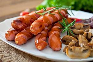 stekt korv med grönsaker på en vit platta foto