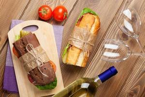 två smörgåsar och vitt vin foto