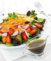 trädgårdssallad med dressing och grönsaker foto