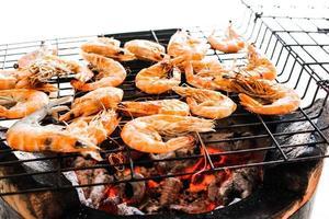 skaldjur läckra grillade räkor, räkor med heta lågor i backg foto