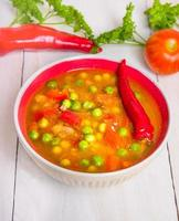minestronsoppa i röd skål på vit träbakgrund foto