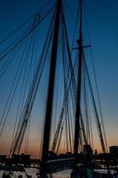solnedgång och segelbåt riggning foto