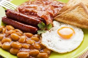 full engelsk frukost med bacon, korv, stekt ägg, bakad bea