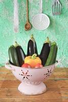 olika grönsaker i en gammal durkslag foto