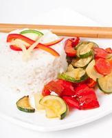 tallrik med grönsaks stekt ris och pinnar.