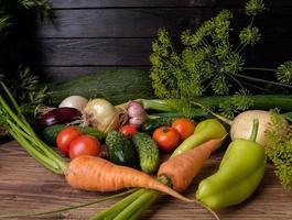 färska grönsaker på ett träbord. foto