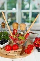 färsk grekisk sallad och ingredienser för matlagning på bordet