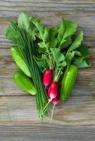 färsk rädisa, gurkor och gräslök foto