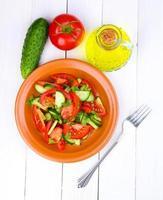 färsk sallad med tomater och gurkor på vit träbakgrund foto
