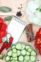 färska skivade grönsaker med kryddor och en anteckningsbok för recept.