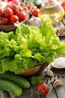 skål med färsk grön sallad, grönsaker, kryddor och olivolja foto